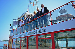 People on the Fjord ship, which advertises Kiel as a science location.
